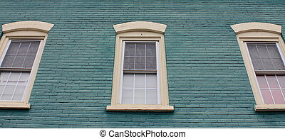 Three windows in a green brick wall