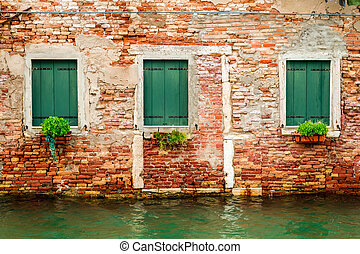 Three windows in ruined house on a canal in Venice
