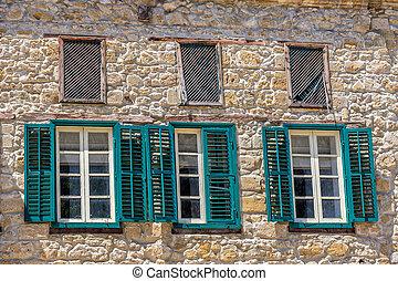 Three windows on facade of house