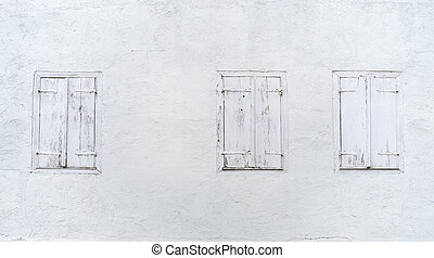 Three windows with closed shutters