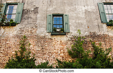 Three Windows with Green Shutters in Old Brick