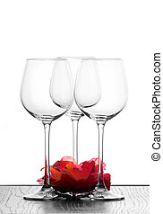 three wine glasses in backlight with red flower