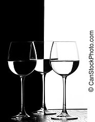 three wine glasses in backlight on the black and white contrast background