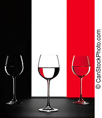 three wine glasses over black white and red background