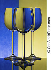 Three wineglasses on a shiny surface with water that distort yellow and blue background