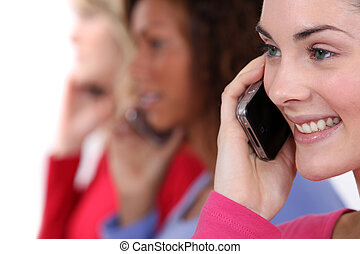 Three woman chatting over the phone.