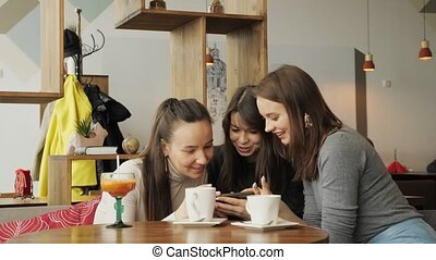 Three woman girlfriends are looking something in smartphone...