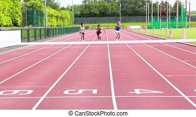 Three woman running on a track and crossing finish line in...