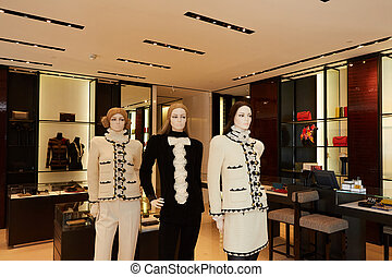 Three womans mannequins in luxury clothes shop.