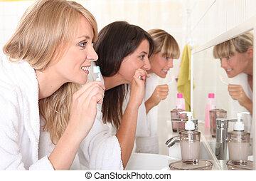 Three women brushing their teeth