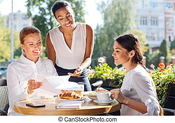 Three women discussing research results during lunch -...
