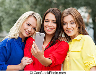 Three women doing a selfie in the park