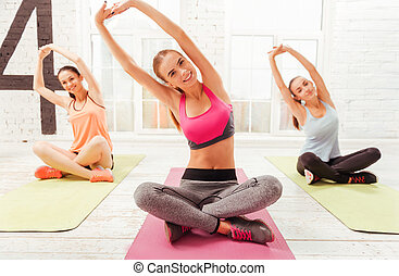 Three women doing stretching with hands up