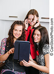 Three women friends chatting at home and using laptop to look at new photo or browsing internet for information