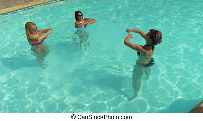 Three women friends doing fitness exercising in the pool water