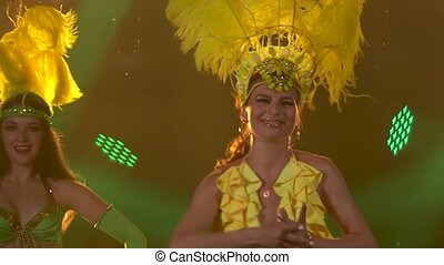 Three women in cabaret costumes with colorful plumage of feathers dance in the studio light. Carnival, party, theatrical show. Close up in slow motion