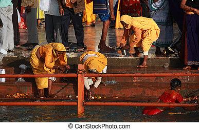Three women in yellow near Ganga during Kumbh Mela festival
