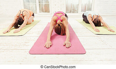 Three women leaning forward while doing stretching