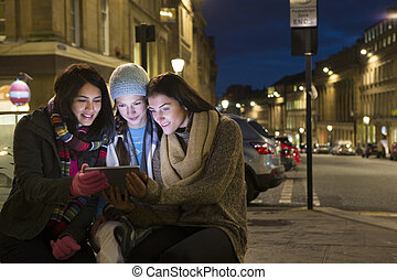 Three women looking at a digital tablet in the city