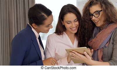 Three women looking at the tablet at the office