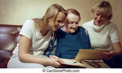 Three women looking through the family archive