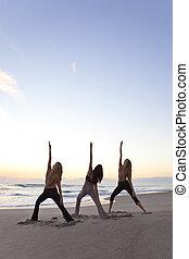 Three Women Practicing Yoga on Beach At Sunrise or Sunset