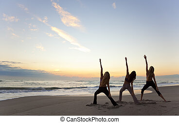 Three Women Practicing Yoga on Beach At Sunrise or Sunset