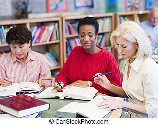 Three women sitting in library with books and notepads (selective focus)