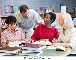 Three women sitting in library with books and notepads while...