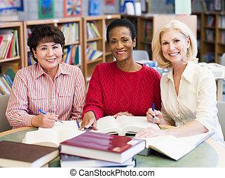 Three women sitting in library with books and notepads...