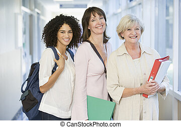 Three women standing in corridor with books (high key)