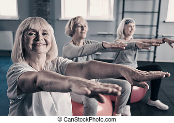 Three women stretching out hands while sitting on exercise balls