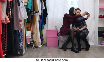 Three women taking a selfie in new dresses while shopping in a clothing store