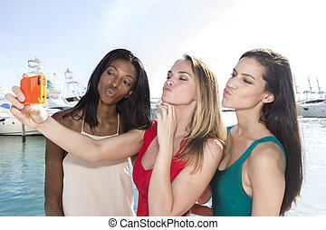 Three women taking duckface selfie