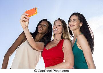 Three women taking selfies