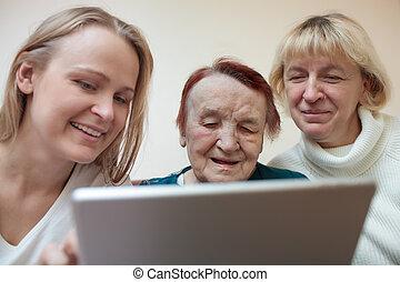 Three women using a smart tablet