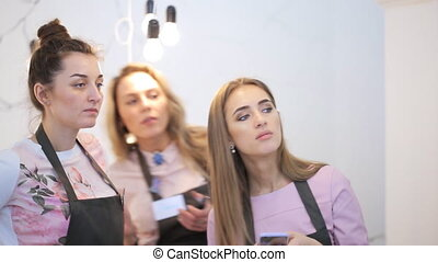 Three women watch process that take place in front of them.