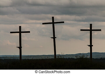 Three Wooden Crosses Stand Against A Dark Ominous Sky