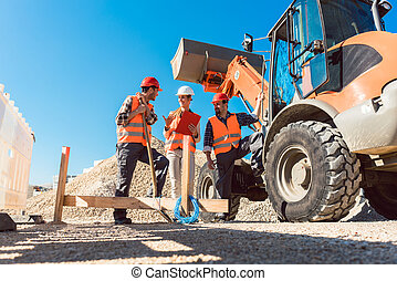 Three workers on roadworks construction site