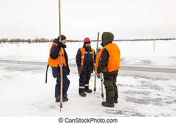 Three workers on the ice of a frozen pond
