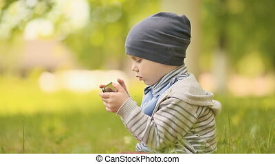 Three-year baby playing with phone on grass