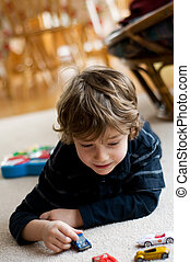 three year old boy laying on the floors playing with his toy cars