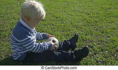 three year old boy sitting on the green grass on a sunny day with a soccer ball