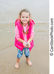 Three year old girl standing on the beach with shells in hand