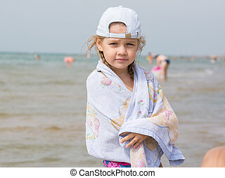 Three year old girl standing on the beach wrapped in a towel
