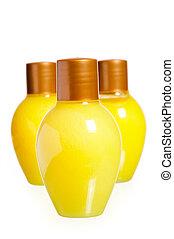 three yellow bottles of cosmetics