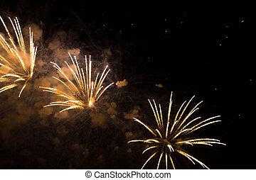 three yellow fireworks in the night sky - three beautiful...