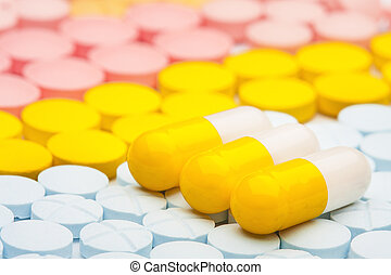 three yellow pills on background of colored medical pills - ...