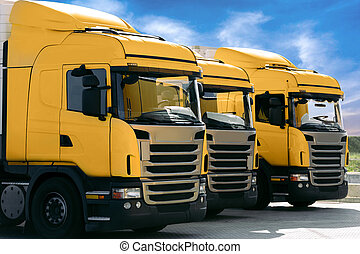 three yellow trucks of a transporting company