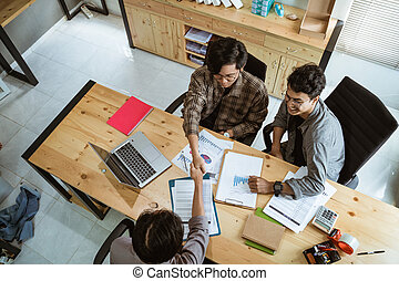 three young Asian business people shook their hands in agreement on a production plan at meeting